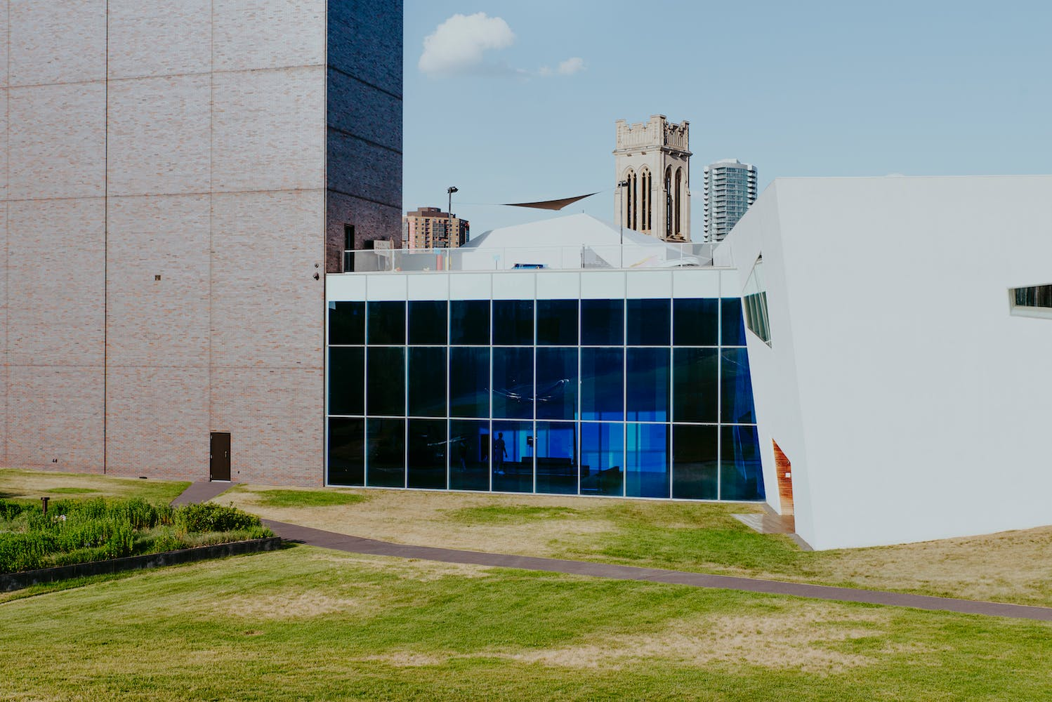 Building with large glass wall covered in blue film, with grass in foreground