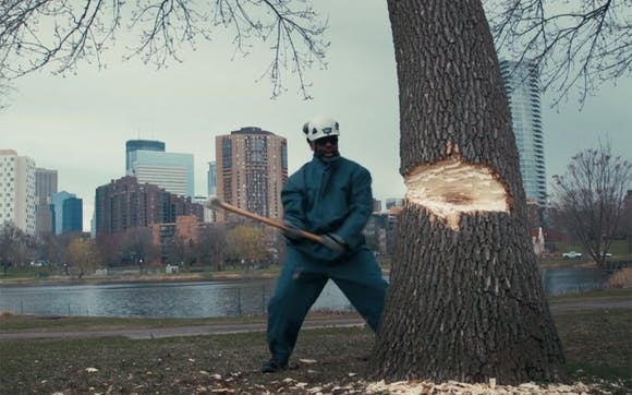 Man Cutting a Tree down with an axe