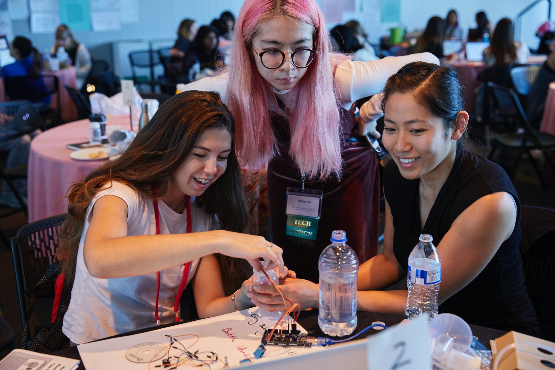 Three young women sitting at a table together working on what appears to be a circuit board.