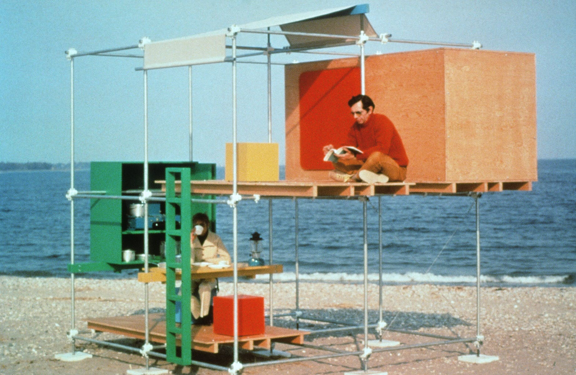Two men sitting in a two-story structure made of metal poles and wooden panels on the beach