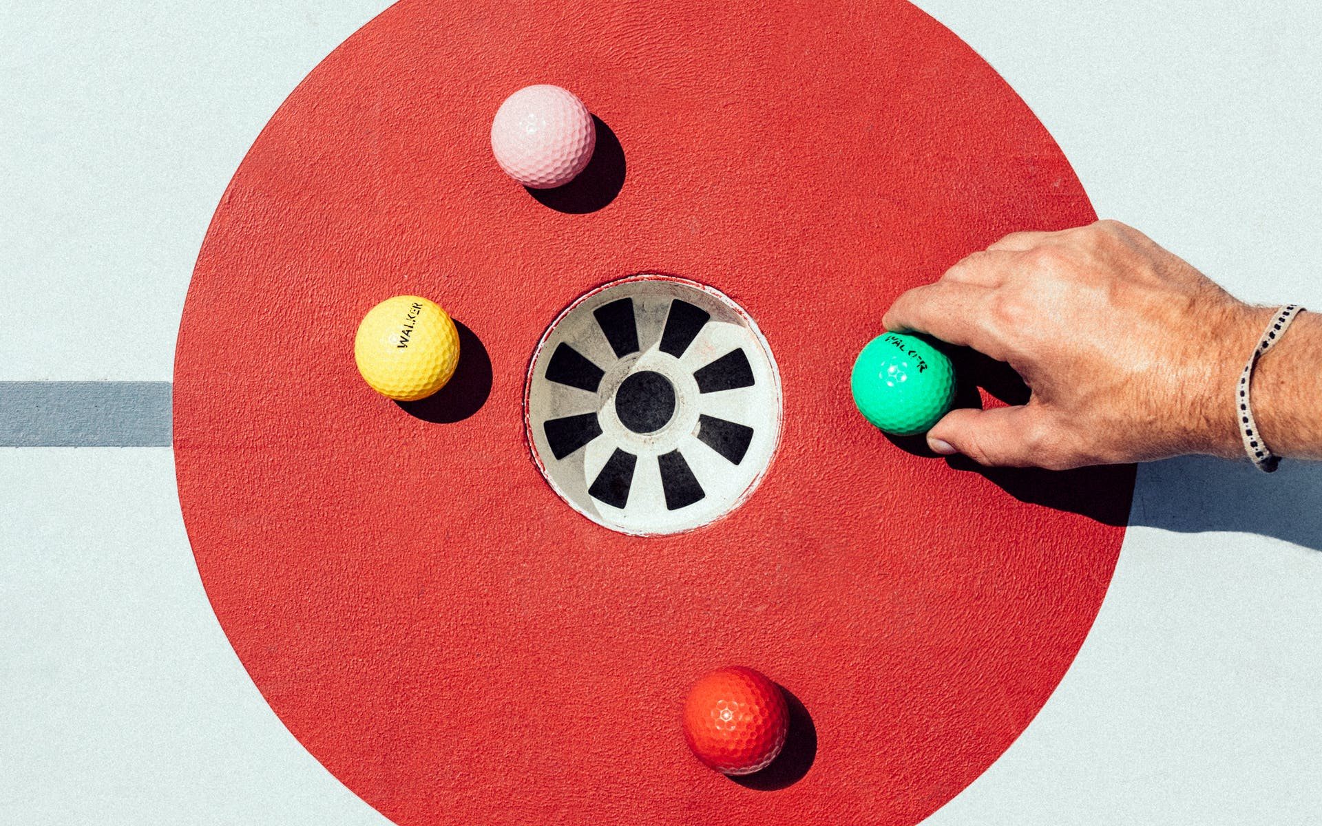 mini golf balls and hole with hand