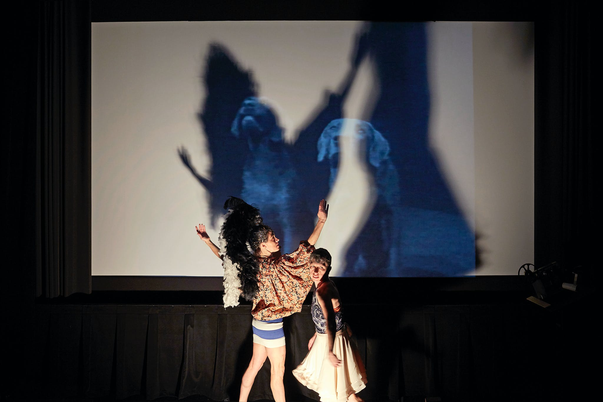 Two dancers in front of a screen.