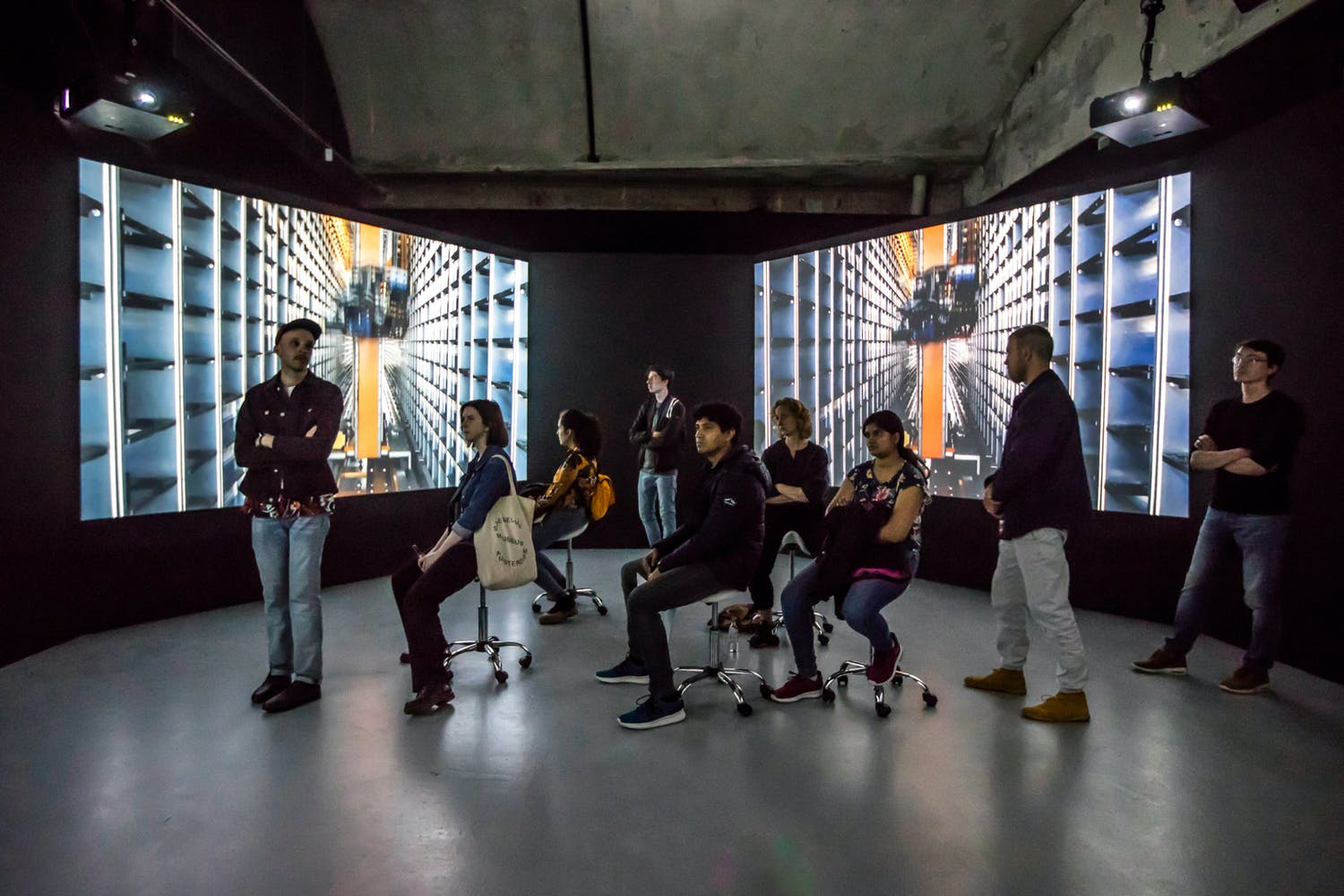Group of people in a gallery surrounded by large projection screens