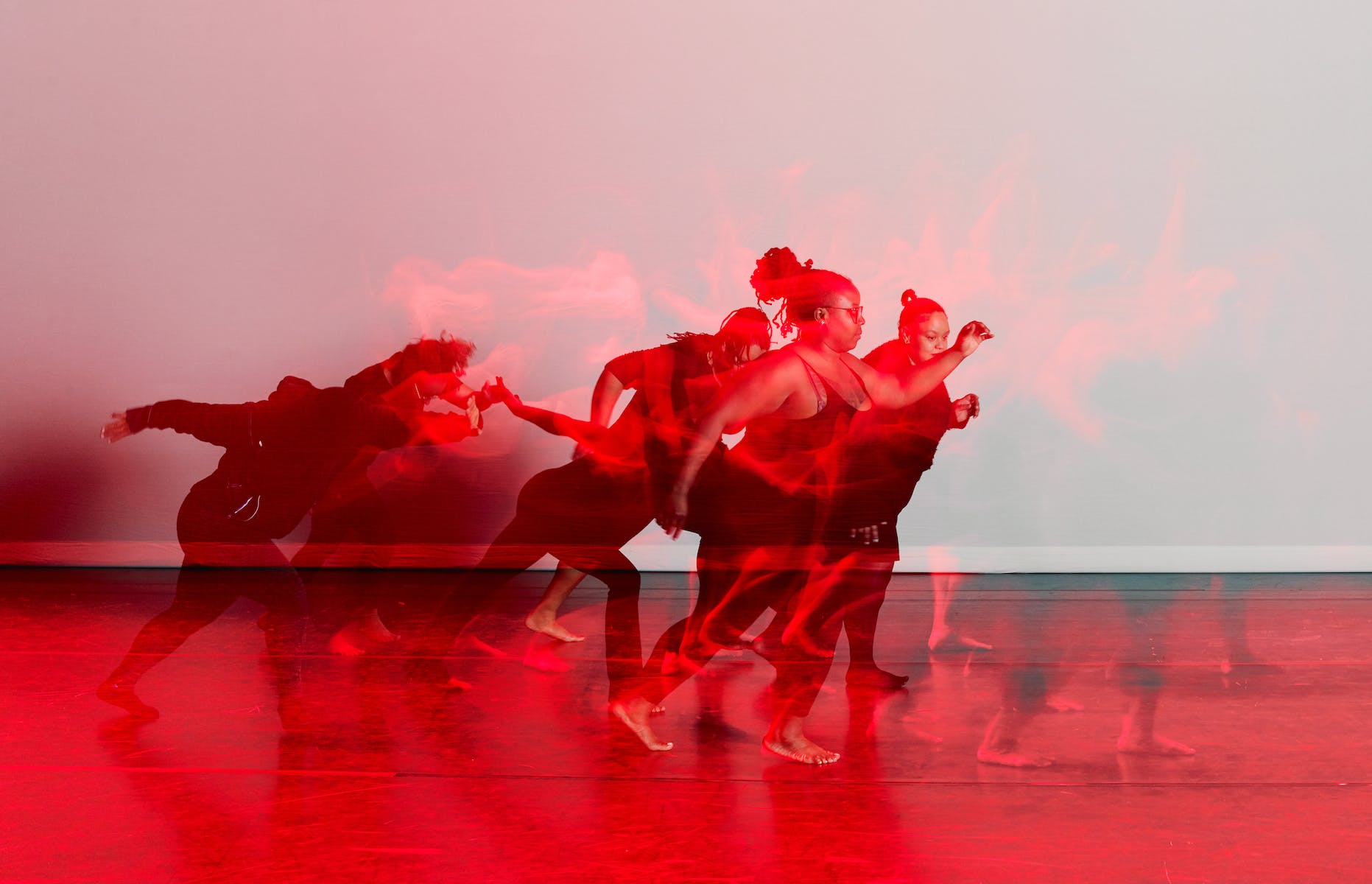Black and red image of dancers on stage.