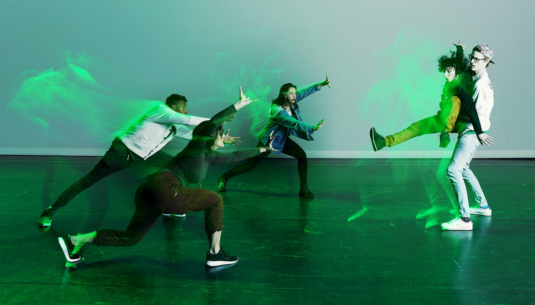 STRONGmovement dance group dancing illuminated by green lighting.