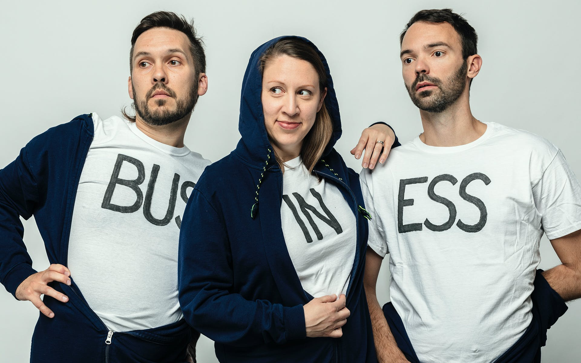 Members of Super Group wearing t-shirts that spell out: BUS IN ESS