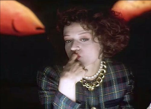 Woman with red curly hair wearing a plaid blazer and gold chain necklacce with her finger in her mouth,