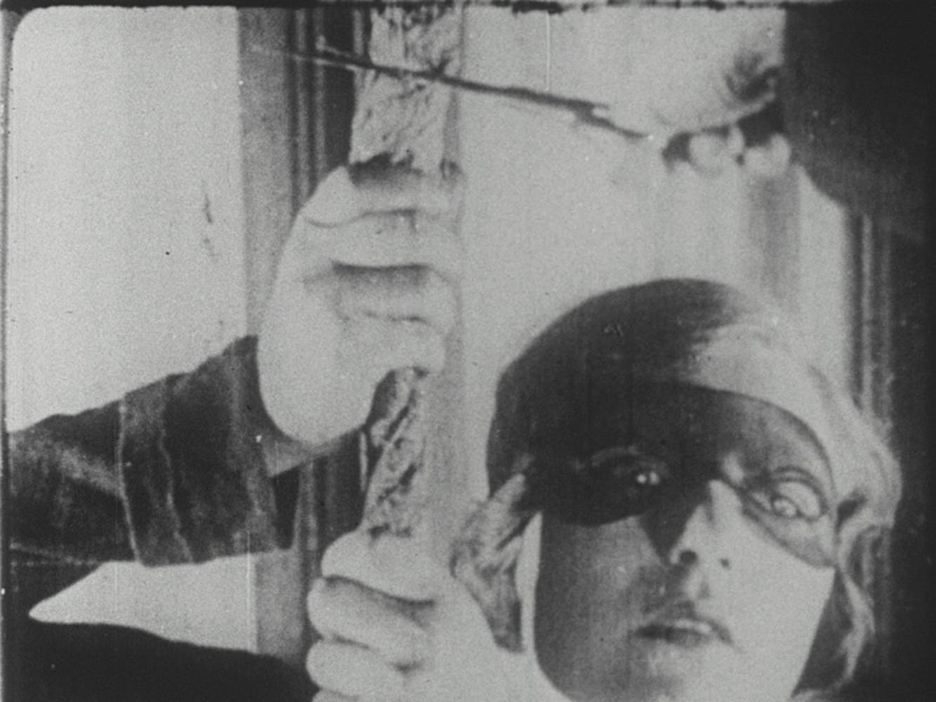 Sepia image of a woman wearing a mask over her eyes, holding onto a rope.
