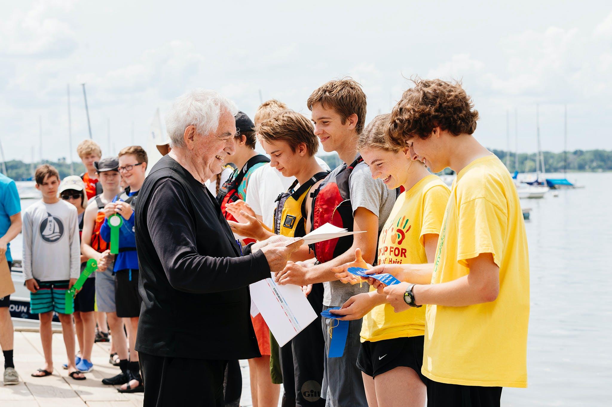 Artist Daniel Buren handing out ribbons to boat race participants.