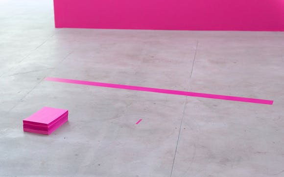 pink paper and lines on a concrete floor