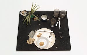 placemat with glasses, silverwar, and a plant
